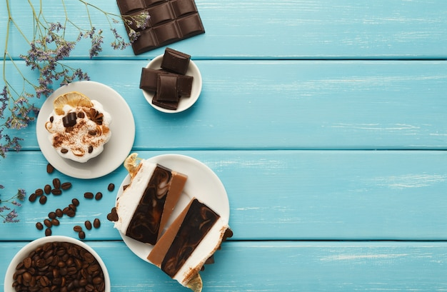 Fond de desserts savoureux. divers gâteaux et barres de chocolat sur une table rustique bleue avec des grains de café épars et des fleurs violettes, style provençal, vue de dessus, espace pour copie