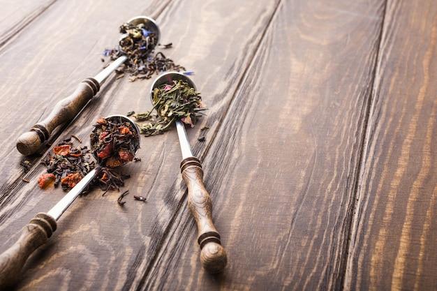 Fond avec différents types de feuilles de thé, noir, vert et fraise sur une table en bois.