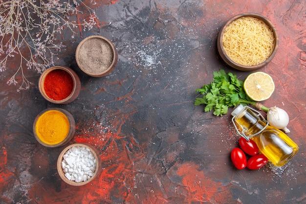 Fond de dîner pâtes non cuites bouteille d'huile de citron vert et différentes épices sur table sombre