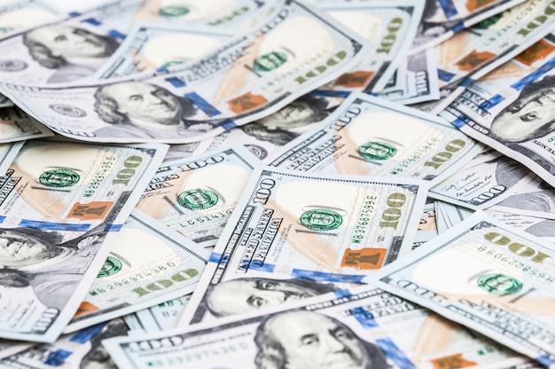 Fond de dollars. des billets de cent dollars américains sont éparpillés dans le fond.