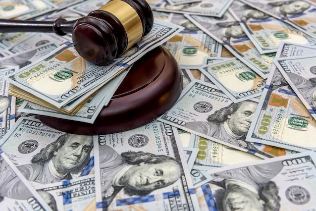 Sur le fond des dollars sont des dollars, et sur eux se trouve le marteau du juge, gros plan