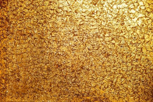 Fond doré. photo conceptuelle. mur de feuille d'or.