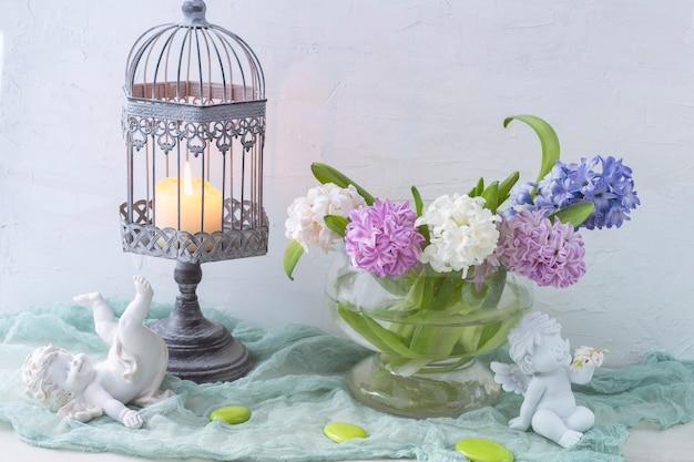 Fond doux avec des anges, des jacinthes et une bougie.