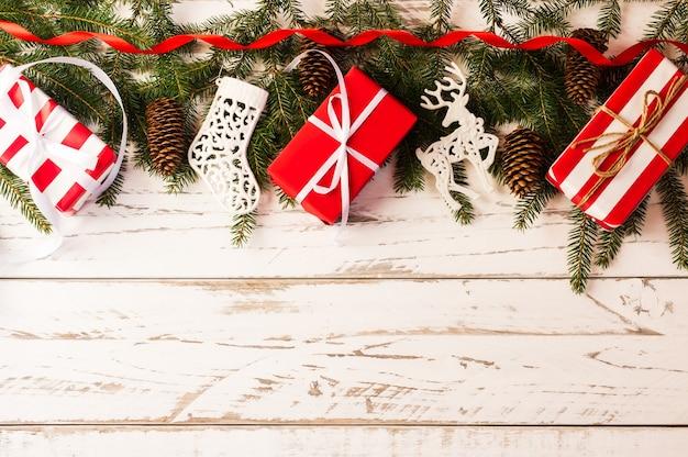 Fond du nouvel an ou de noël avec une copie de l'espace. cadeaux de boîtes de vacances, branches d'épinette, cônes sur une table en bois blanc.