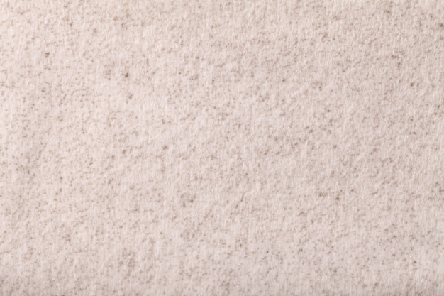 Fond duveteux beige clair en tissu doux et moelleux. texture de textile crème.