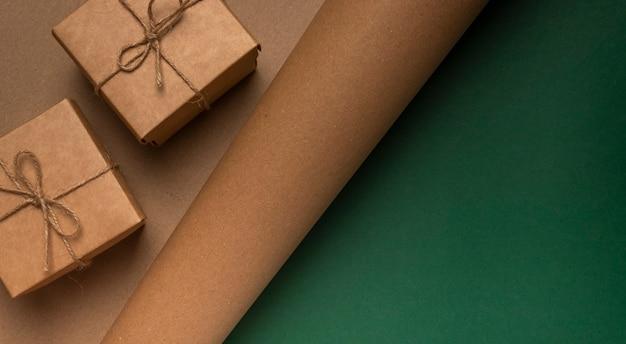 Fond eco de texture en carton artisanal avec deux coffrets cadeaux et fond vert.