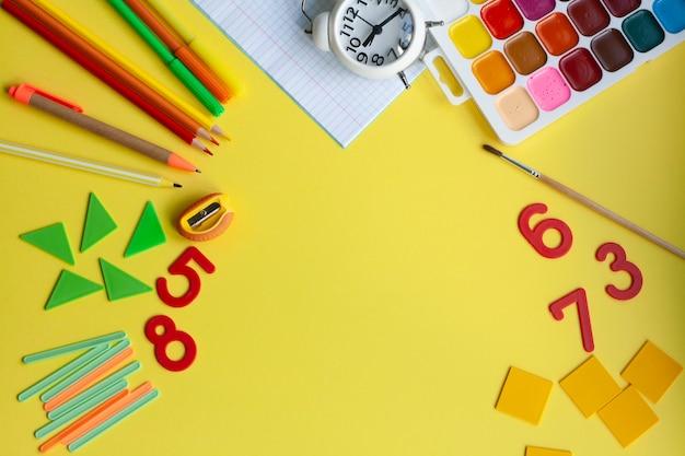 Fond d'école avec des fournitures scolaires sur jaune, plat, espace de copie