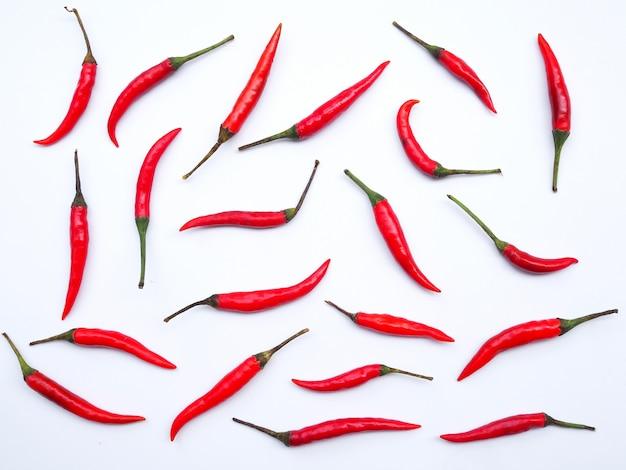 Fond d'écran avec des piments rouges chauds isolés sur mur blanc.