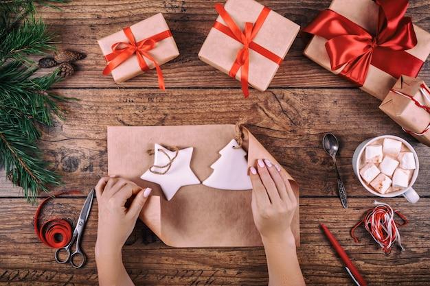 Fond d'emballage cadeau. mains féminines emballant des décorations de noël faites à la main au cadeau de noël en papier kraft