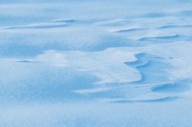 Fond enneigé, surface enneigée de la terre après un blizzard le matin au soleil avec des couches distinctes de neige