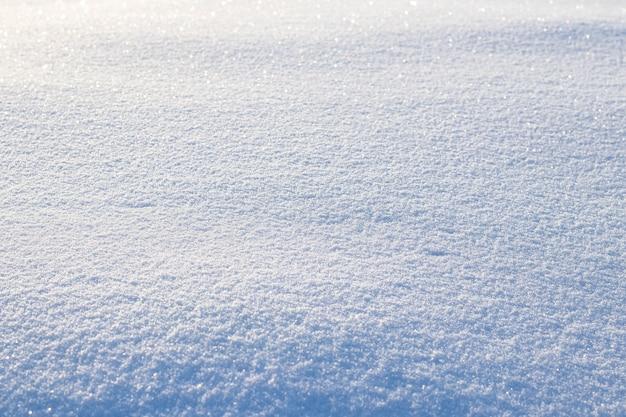 Fond enneigé, surface enneigée avec une texture clairement exprimée de neige au soleil du matin
