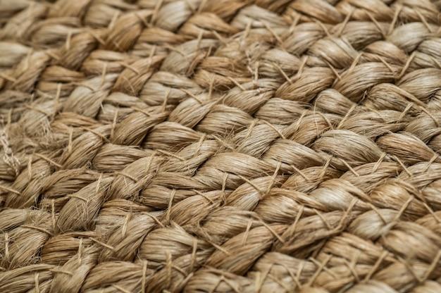 Fond entrecroisé avec des basiques de paille, sac avec de la paille, fait main, artisanat. texture de sacs de paille peints se bouchent.