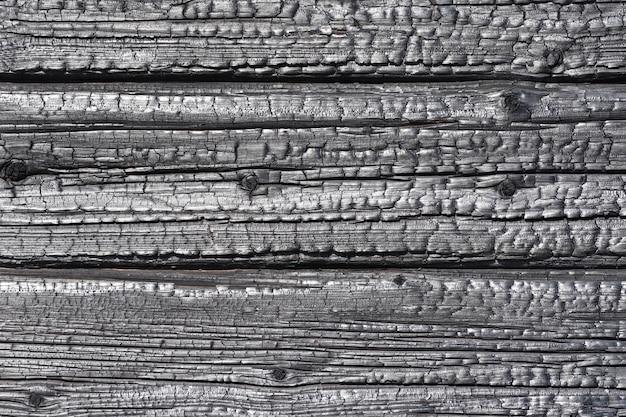 Fond est la texture de bûches de mur de maison en bois brûlé