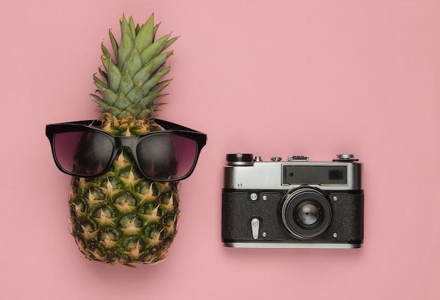 Fond d'été. amusement et humour. concept de voyage. ananas avec appareil photo rétro lunettes de soleil