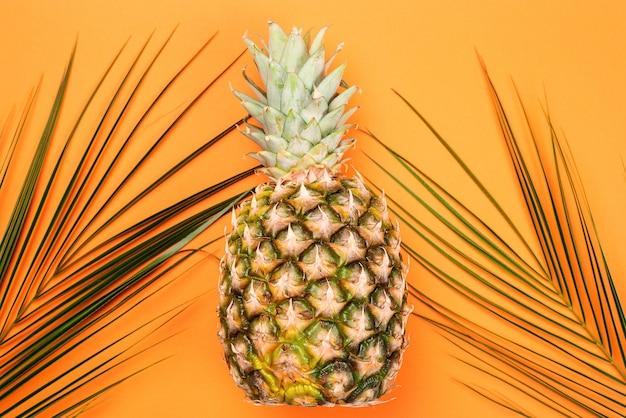 Fond d'été avec des feuilles d'ananas et de palmier. mise à plat créative, vue de dessus. style minimaliste.