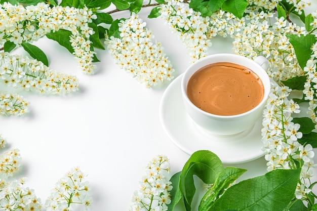 Fond d'été avec des fleurs et du café sur fond blanc. vue latérale, copiez l'espace.