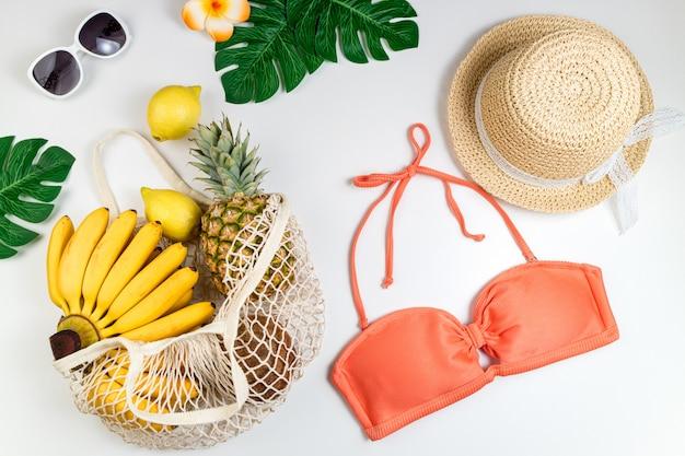Fond d'été maillot de bain femme accessoires de plage, fruits tropicaux dans un sac écologique, feuilles de palmier sur blanc
