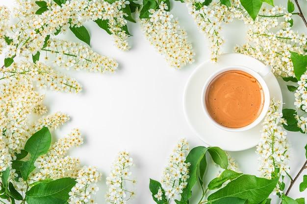 Fond été-printemps avec des branches fleuries et une tasse de café sur fond blanc. vue de dessus, copiez l'espace.