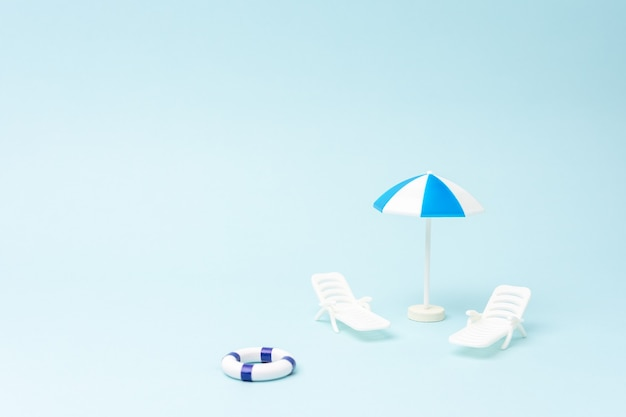 Fond d'été avec transats parasol et anneau de natation sur fond bleu pastel