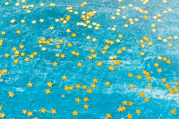 Fond avec des étoiles d'or arrangées au hasard