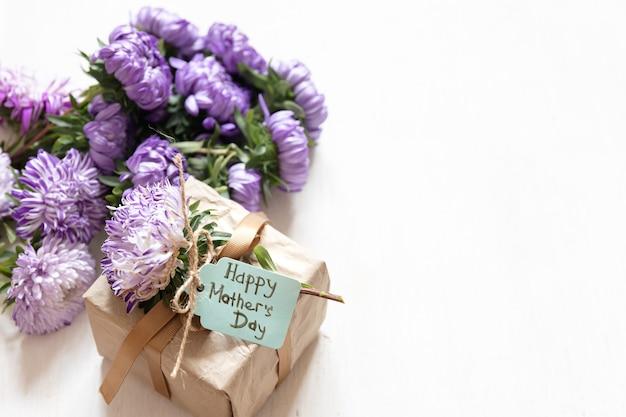 Fond festif de la fête des mères avec boîte-cadeau et fleurs de chrysanthème fraîches sur fond blanc, espace de copie.
