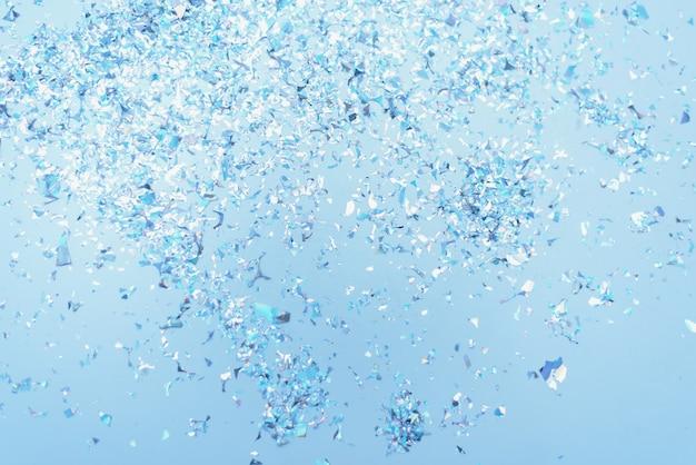 Fond festif pastel bleu avec des confettis et des étincelles. style plat