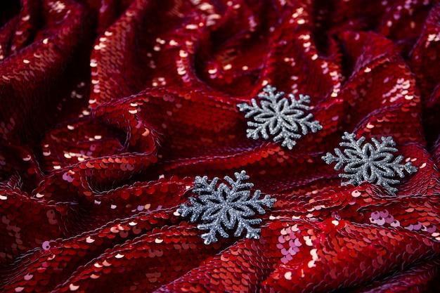 Fond festif rouge avec des paillettes et trois décorations en argent pour noël