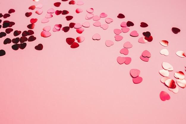 Fond festif rouge et rose avec des confettis en forme de coeur rouge.