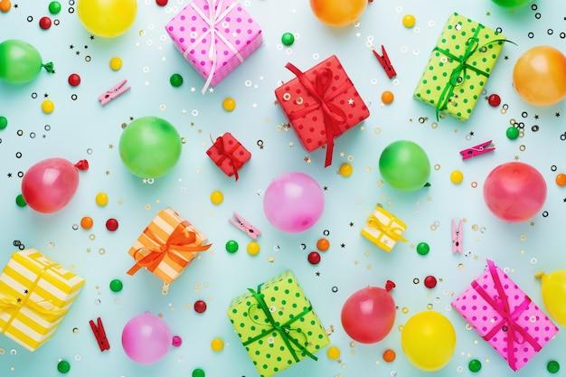 Fond de fête d'anniversaire avec des coffrets cadeaux colorés et des décorations sur fond bleu
