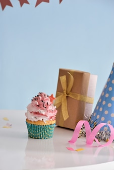 Fond de fête d'anniversaire avec cupcake, chapeau de fête et cadeau