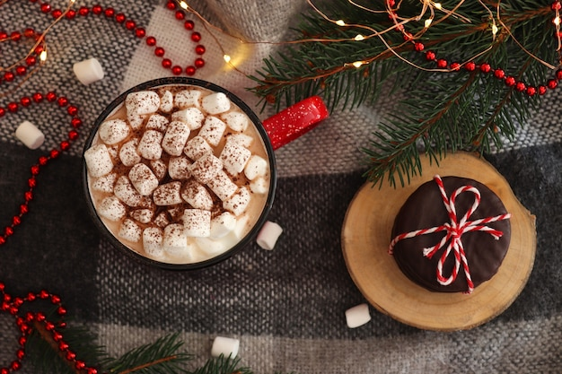 Fond de fête avec des branches d'arbres de noël et du chocolat chaud avec des guimauves sur plaid