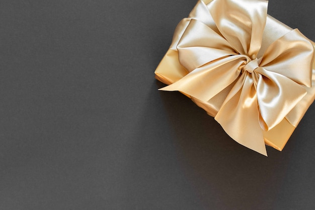 Fond de fête avec cadeau en or, boîte avec ruban d'or et arc sur fond noir, mise à plat, vue de dessus, espace copie