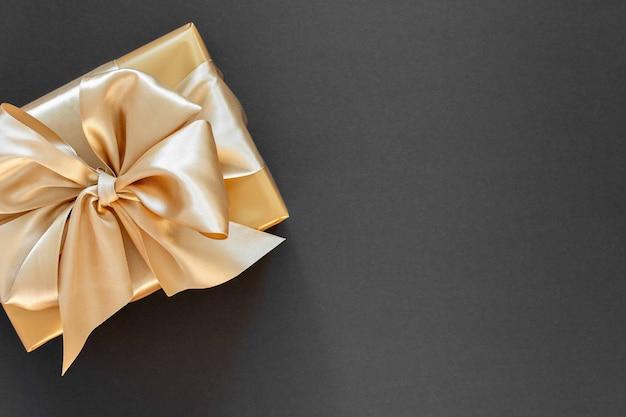 Fond de fête avec cadeau en or, boîte avec ruban d'or et arc sur fond noir, mise à plat, vue de dessus, espace de copie