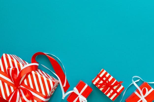 Fond de fête avec des cadeaux, boîte-cadeau avec ruban et arc sur un fond bleu turquoise, mise à plat, vue de dessus