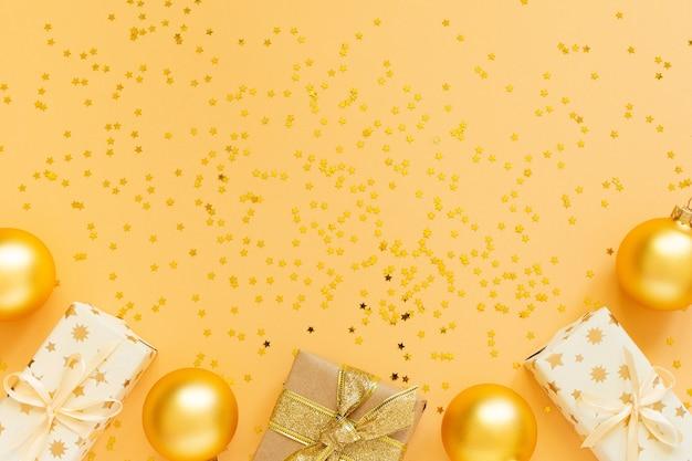 Fond de fête, coffrets cadeaux et boules de noël sur fond avec des étoiles d'or scintillantes, mise à plat, vue de dessus, espace copie
