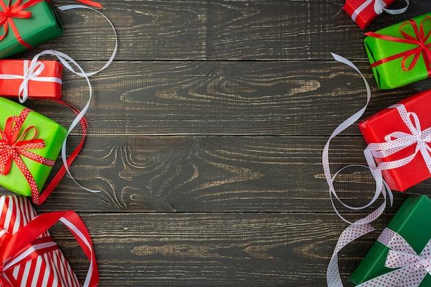 Fond de fête, coffrets cadeaux colorés et rubans sur un fond en bois brun, saint valentin ou anniversaire, joyeux noël