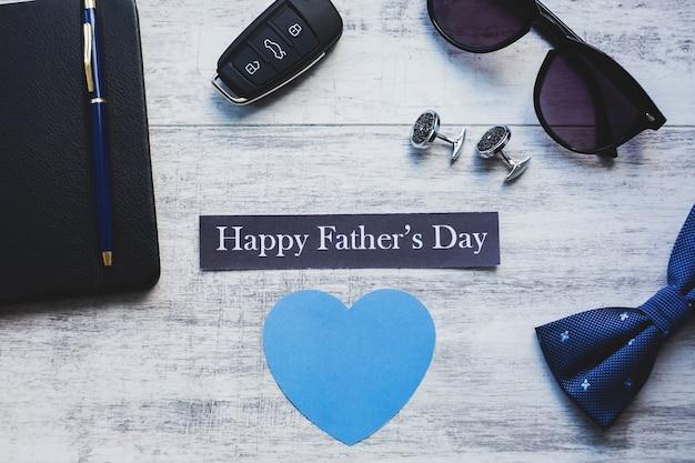Fond de fête des pères heureux. bouton de manchette, clé de voiture, nœud papillon, stylo et lunettes de soleil.