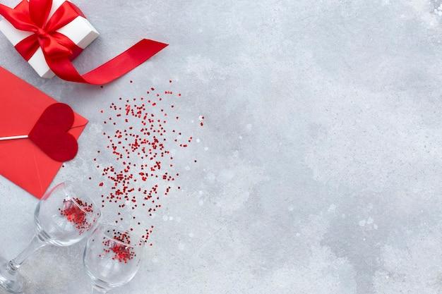 Fond de fête de la saint-valentin, sur fond de pierre grise, enveloppe rouge avec coeur, boîte-cadeau blanche avec arc rouge et verres de vigne vue de dessus