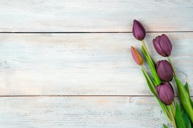 Fond de fête avec des tulipes violettes sur un fond en bois clair.
