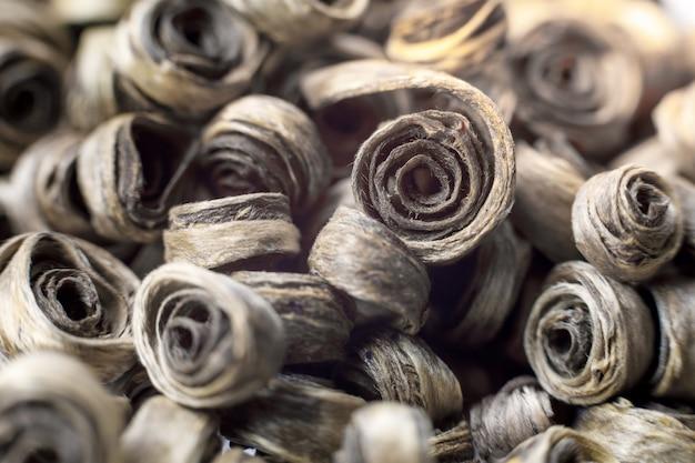 Fond de feuilles sèches torsadées de thé vert. le thé vert est l'antioxydant le plus puissant.