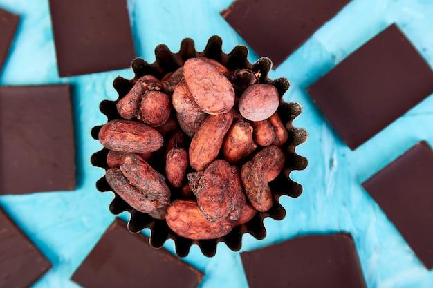 Fond de fèves de cacao sur le tableau bleu. morceaux de chocolat noir