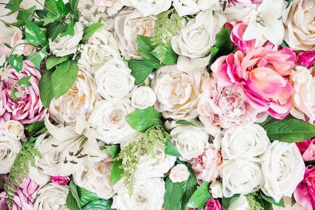 Fond de fleurs artificielles de roses blanches et roses et de feuilles vertes.