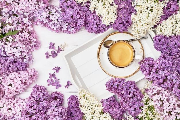 Fond de fleurs lilas avec une tasse de café au milieu