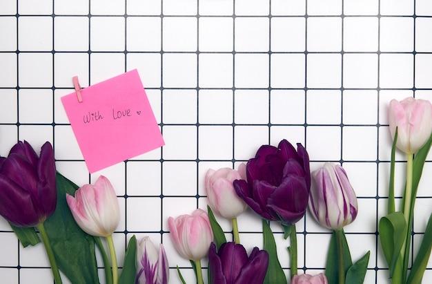 Fond floral de printemps avec espace de copie. cadre à plat fait de fleurs de fleurs de tulipes avec des gouttes d'eau