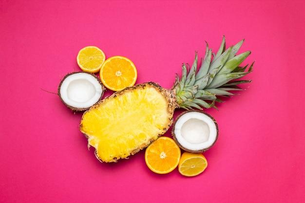 Fond de fruits ananas, noix de coco sur fond rose. fruits d'été. lay plat, vue de dessus, espace de copie