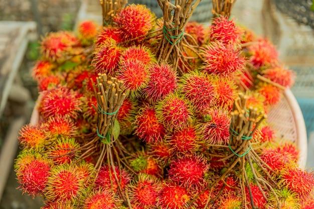 Fond de fruits frais ramboutans, ramboutans rouges et ramboutans jaunes sur un marché local,
