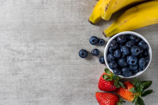 Fond avec des fruits frais et sains sur une table en bois. bananes, myrtilles et fraises. vue de dessus. copiez l'espace.