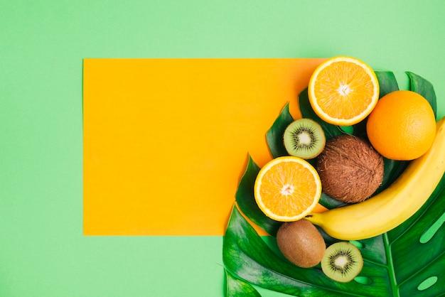 Fond de fruits tropicaux avec gabarit de carte et feuille de palmier