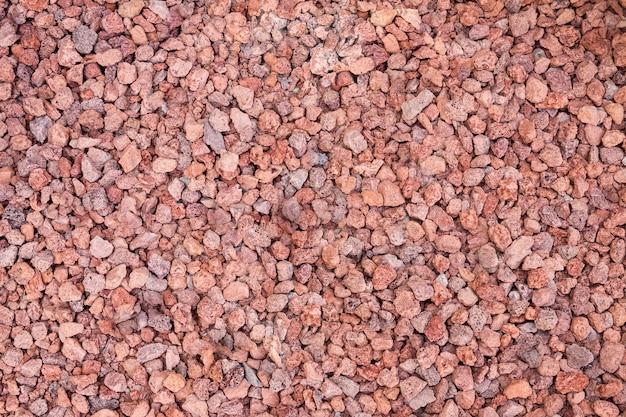 Fond de galets rouges, gros plan de la roche rouge écrasée.
