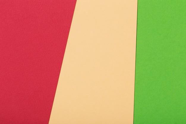 Fond géométrique de feuilles de carton rouge, vert et beige clair